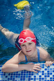 Young happy girl learning to swim in the pool with flippers royalty free stock photography
