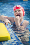Young happy girl learning to swim in the pool with foam board royalty free stock photo