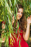 Young happy girl in the leaves of the willow Royalty Free Stock Image