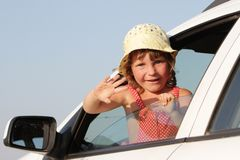 Young happy girl looking out from car window Stock Photos