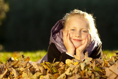 Young happy girl lying on floor in autumn leaves Royalty Free Stock Photo