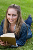 Young happy girl lying on the grass while holding a book and loo Stock Image