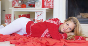 Young happy girl lying on red blanket next to fireplace Stock Photo