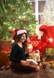 Young, happy girl  near the christmas tree with presents. Young, happy girl opening her christmas present near the christmas tree with presents. Studio shoot Stock Photos