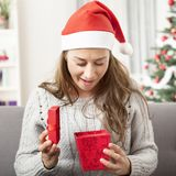 Young happy girl opens christmas gift Royalty Free Stock Image