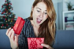 Young happy girl opens christmas gift Stock Images