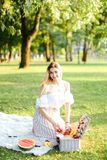 Young happy girl preparing forpicnic in park, sitting on plaid near box and waterlemon. stock photo