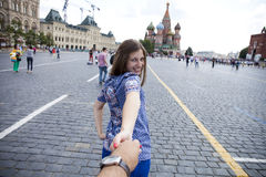 Young happy girl pulls the guys hand on the Red Square in Moscow Stock Photo