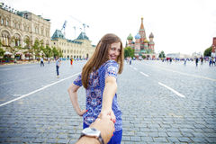 Young happy girl pulls the guys hand on the Red Square in Moscow Royalty Free Stock Photography