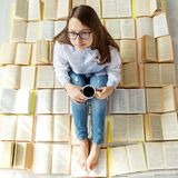 Young happy girl reading a book and drinking coffee. View from above. Concept for World Book Day, lifestyle, study, education stock photos