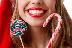 A happy girl with red lips is holding close by the face of two Christmas candies and a cute smile. Close-up. stock image