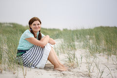 Young happy girl relaxing on sand dunes of the beach of St.Peter Royalty Free Stock Photo