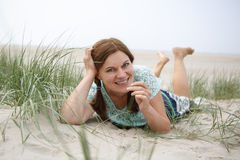 Young happy girl relaxing on sand dunes of the beach of St.Peter Royalty Free Stock Image