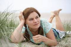 Young happy girl relaxing on sand dunes of the beach of St.Peter Royalty Free Stock Photography