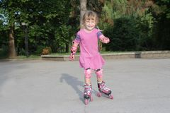 Young happy girl riding roller blades Stock Photo