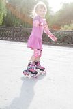 Young happy girl riding roller blades Stock Photos