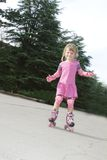 Young happy girl riding roller blades Royalty Free Stock Image