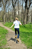 Young happy girl running at green park. Young happy blonde girl running at green park Royalty Free Stock Photos