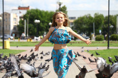 Young happy girl runs through a flock of pigeons on the square Royalty Free Stock Photography