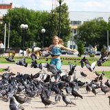 Young happy girl runs through a flock of pigeons on the square Stock Images
