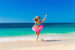 Young happy girl runs out of the tropical sea with rubber ring. royalty free stock photo