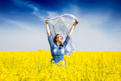 Young happy girl with a scarf in the field Royalty Free Stock Photography