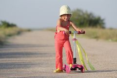 Young happy girl on scooter on road Stock Photography
