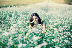 Girl sits on the buckwheat field Royalty Free Stock Photo