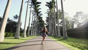 Young happy girl spinning around with spreading hands at coconut plantation. Tourist woman dancing near palm trees. Peradeniya, Sri Lanka stock footage