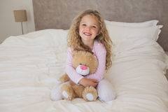 Young happy girl with stuffed toy sitting on bed Royalty Free Stock Image