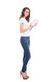A young and happy girl in stylish jeans holding a tablet compute Royalty Free Stock Photos