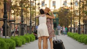 Young Happy Girl With Suitcase Meets Female Friend. They speak about holiday. Happy female friends meeting in the city after enjoying a trip stock video
