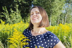 Young happy girl surrounded by bright yellow flowers Royalty Free Stock Image
