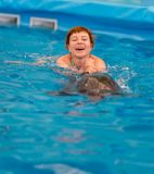 Young happy girl swimming with dolphin. In swimming pool royalty free stock images