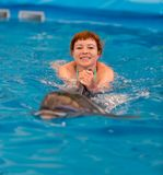 Young happy girl swimming with dolphin. In swimming pool stock image