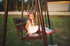 Young happy girl on the swings Royalty Free Stock Image