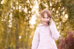 Young happy girl talks cellphone. Phone roaming. People with smartphone. Autumn background royalty free stock photos