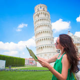 Young happy girl with toristic map on travel to Pisa. Tourist traveling visiting The Leaning Tower of Pisa. royalty free stock image