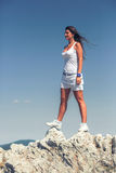 Young happy girl tourist standing on top of a mountain and looki Stock Photos