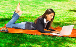 Young and happy girl using her laptop in the park Royalty Free Stock Images