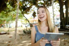 Young happy girl using tablet and riding swing on sand, wearing jeans sundress. royalty free stock photos