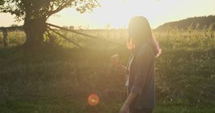 Young happy girl walking and eating red apple, natural healthy food on nature. Rural landscape golden hour stock video footage