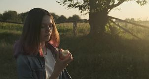 Young happy girl walking and eating red apple, natural healthy food on nature. Rural landscape golden hour stock footage