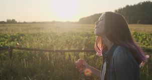 Young happy girl walking and eating red apple, natural healthy food on nature. Rural landscape golden hour stock video