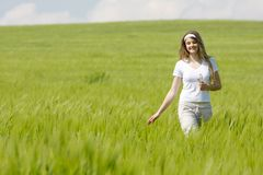 Young happy girl walking in field Stock Images