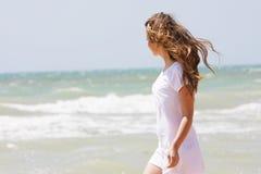 Young happy girl walking on sea Stock Photo