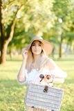 Young happy girl wearing hat standing in park with bag. Young happy woman wearing hat and dress standing in garden with bag. Concept of beautiful female person stock photography