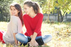 Young happy girls in autumn park outdoor portrait Stock Photo