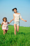 Young happy girls running at green wheat field Royalty Free Stock Photos