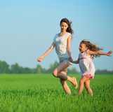Young happy girls running at green wheat field Royalty Free Stock Image
